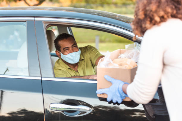 Man in car wears mask while receiving box of food During the coronavirus epidemic a mature adult man wears a mask while receiving a box of food. food drive stock pictures, royalty-free photos & images