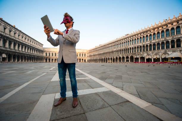 Man in Carnival Mask Using Tablet Venice Italy stock photo