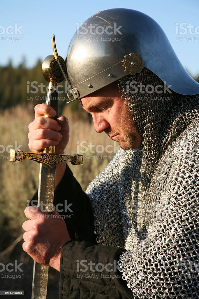 Man in chain mail kneeling and gripping a sword stock photo