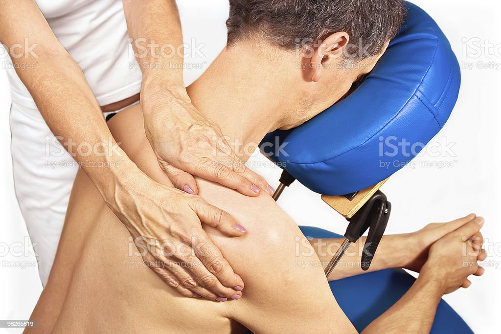 Man in chair gets massage on shoulders royalty-free stock photo