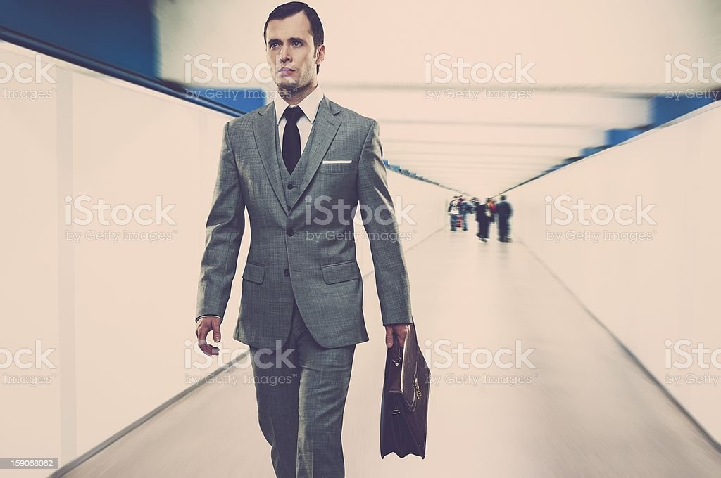 Man in classic grey suit with briefcase walking through corridor stock photo