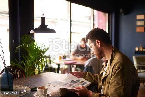 Male person sitting in cafeteria and reading some magazine while having a coffee.
