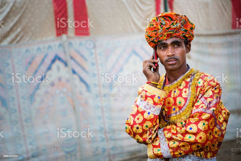 man in colorful dress with mobile phone in pushkar camel fair stock photo