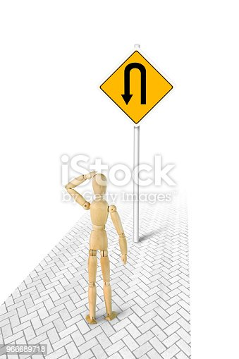Man in confusion standing in front of Turn Back road sign. Conceptual image with a wooden puppet