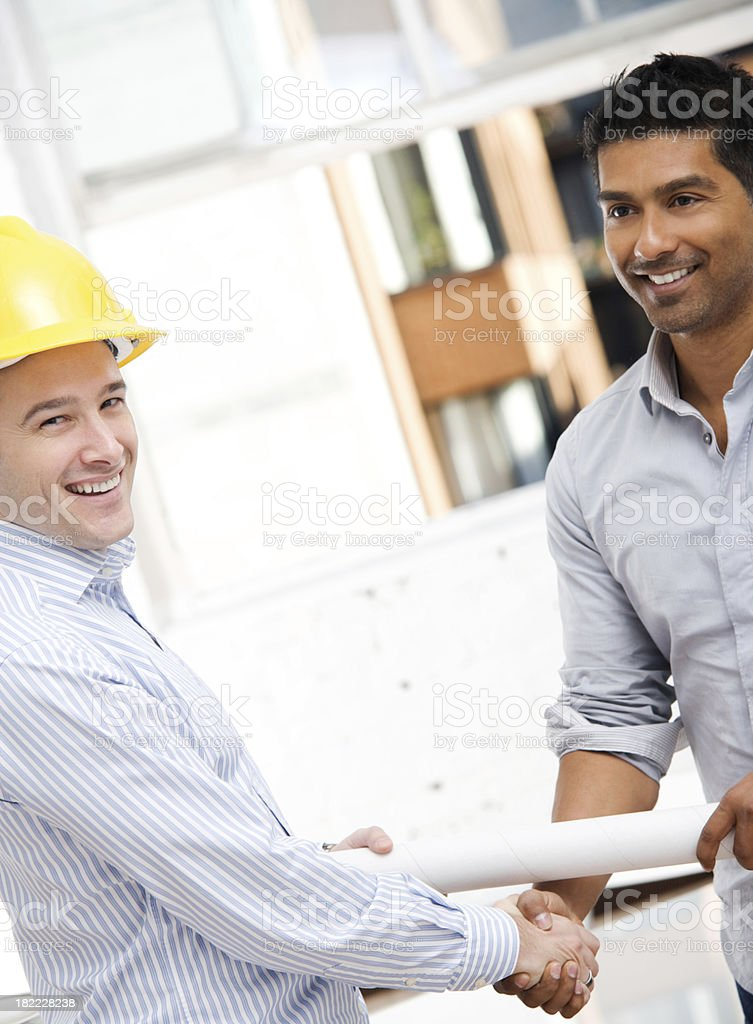 Man in Construction Hat Shaking Hands with Architect or Engineer royalty-free stock photo