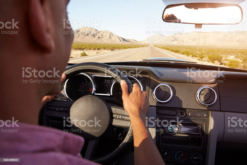 Man In Convertible Car Driving Along Open Road stock photo