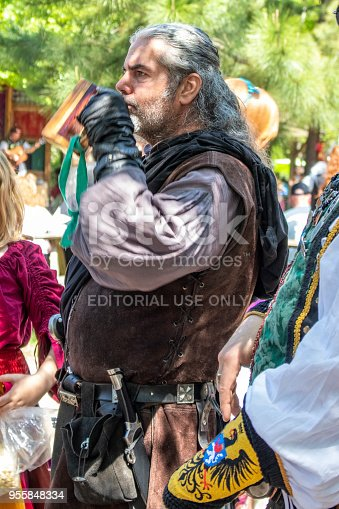 Man in costume with long grey hair taking a drink from a wooden cup with other fair-goers in background at Oklahoma Renaissance Festival Muskogee Oklahoma 5 5 2018