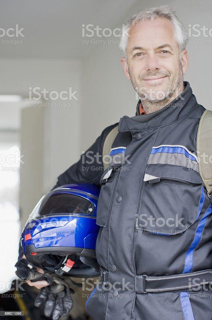 Homme en combinaison tenant un casque et des gants photo libre de droits