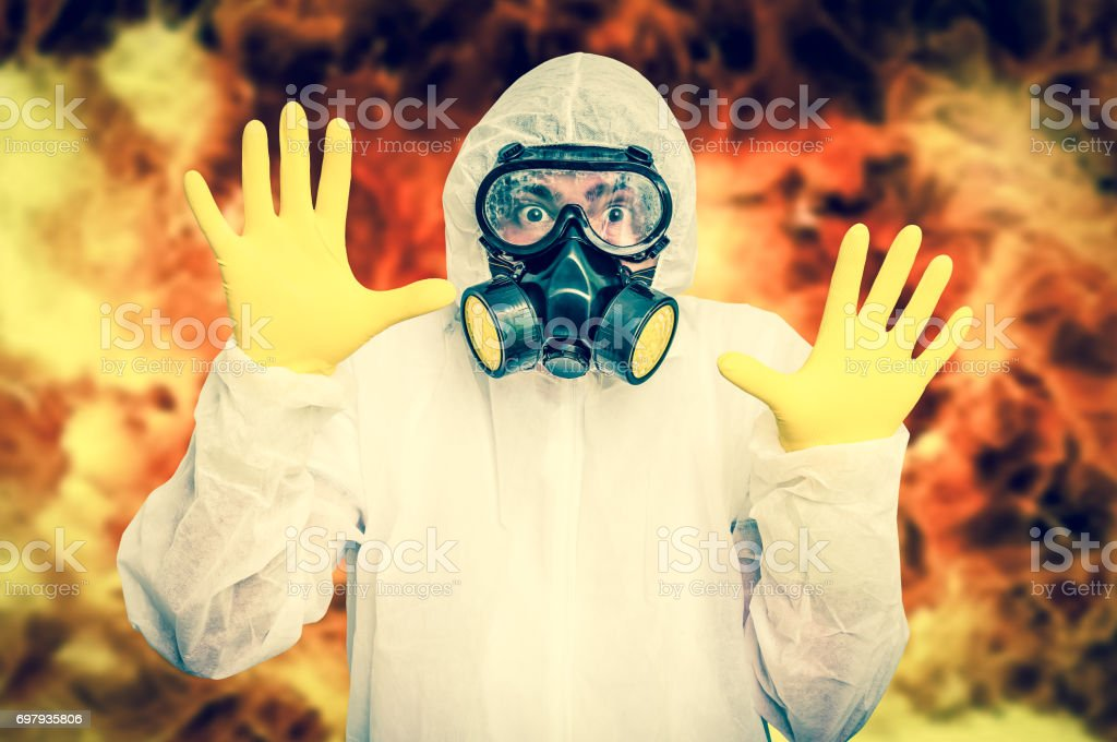 Man in coveralls with gas mask is showing stop gesture stock photo