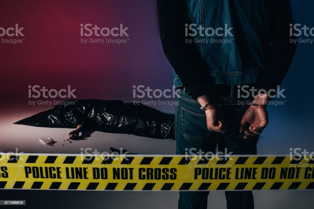 Man in cuffs by dead body behind yellow line on dark background stock photo