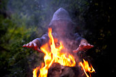 Man in darkness warming his hands near the campfire.Focus on hands.