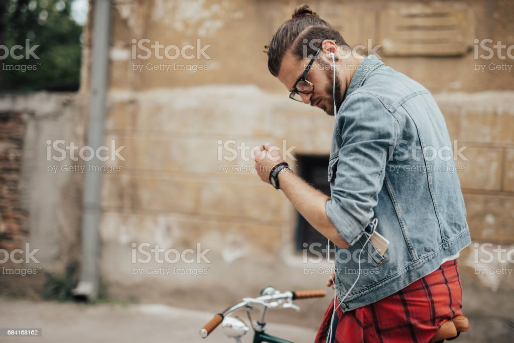 Man in denim jacket listens to podcast and rides a bicycle to his office royalty-free stock photo