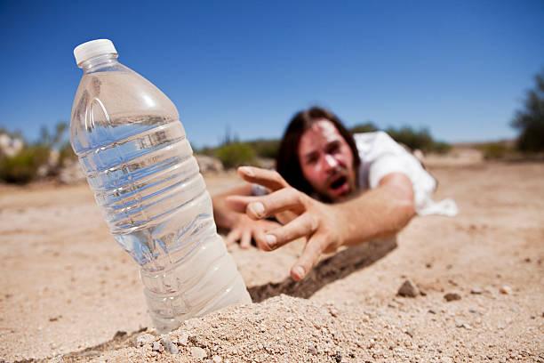 man in desert reaching for water - kuraklık stok fotoğraflar ve resimler