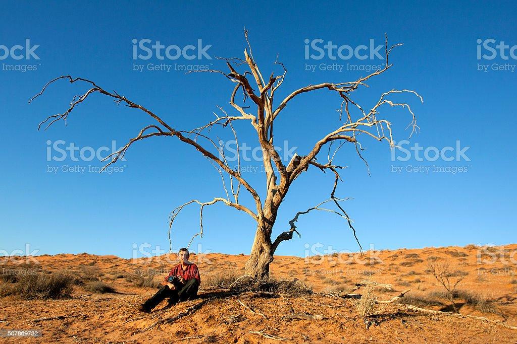 Man in Desert with Tree stock photo