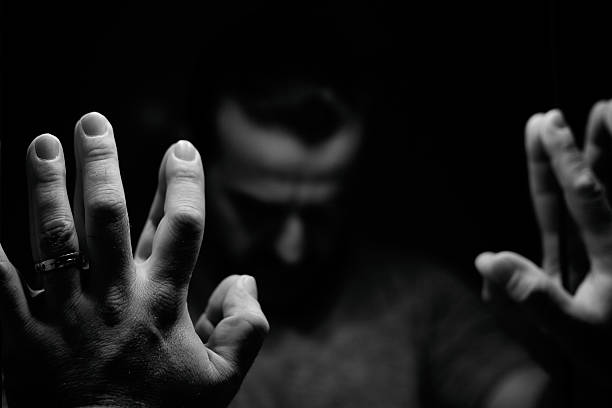 Man in despair with raised hands and bowed head Man in despair with raised hands and bowed head, monochromatic image in a low light room looking in front of mirror guilty stock pictures, royalty-free photos & images
