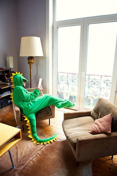 homme en costume de dinosaure détendre à la maison à l'aide d'une tablette numérique - mascotte photos et images de collection