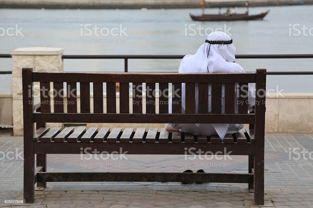 Man in dishdasha sitting on a bench at Creek, Dubai stock photo