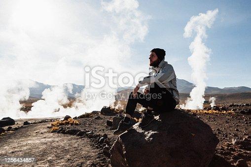 Young Caucasian man enjoying the beautiful view of El Tatio geyser field at sunrise in mountains in Atacama, Chile