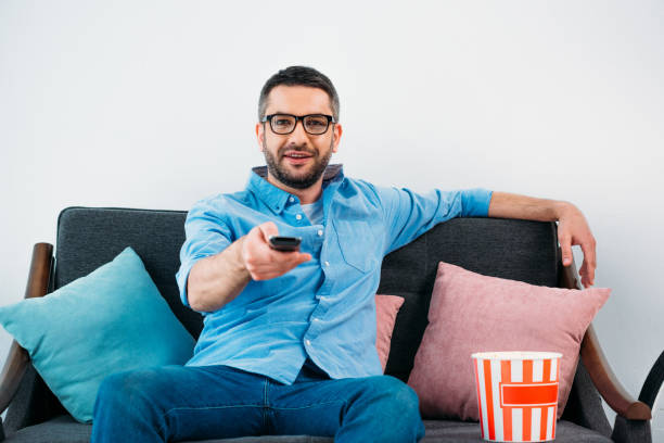 man in eyeglasses resting on sofa and watching tv at home stock photo