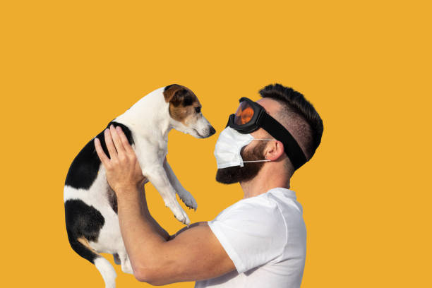 man in face mask and protective glasses holding up cute near face - covid hair imagens e fotografias de stock
