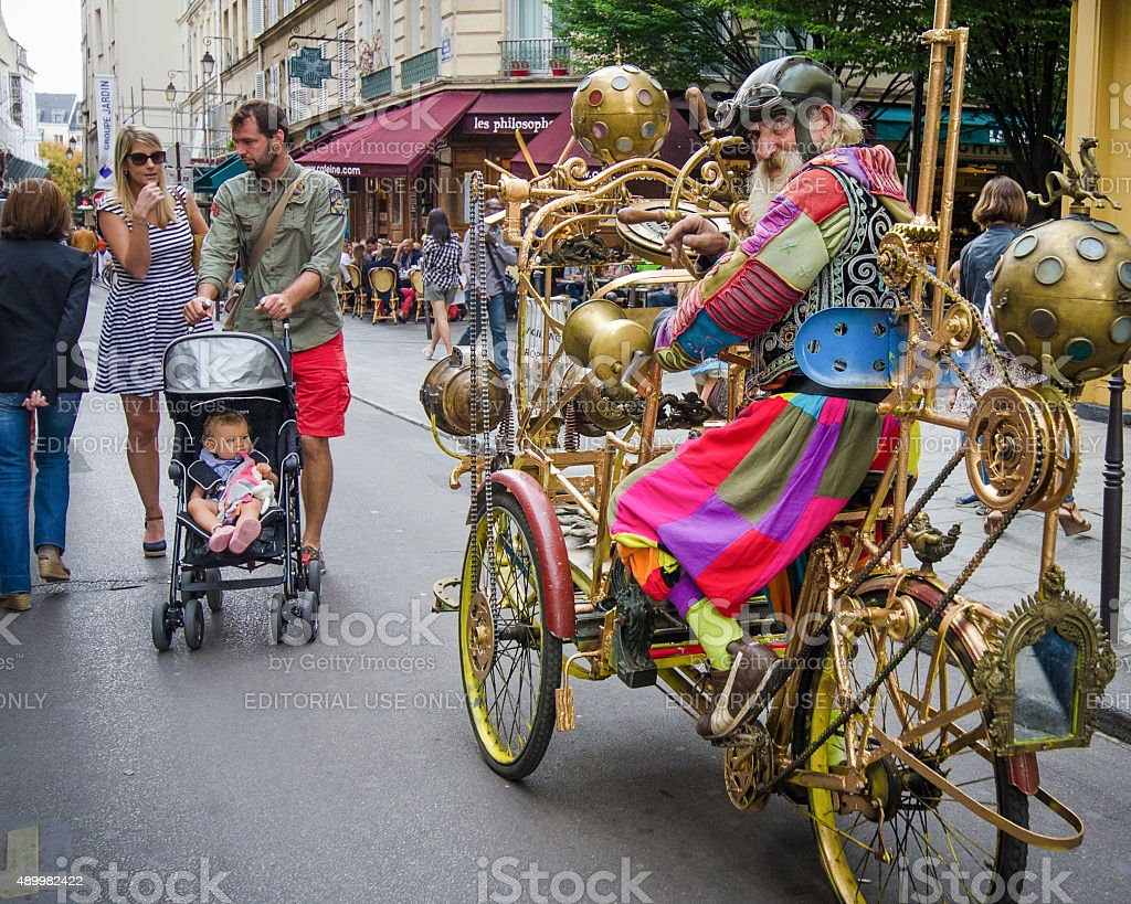 Man in fanciful Jules Verne costume rides cycle in Marais stock photo