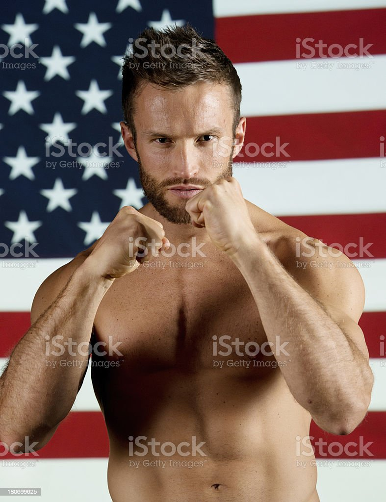 Man in fighting pose with american flag behind him royalty-free stock photo