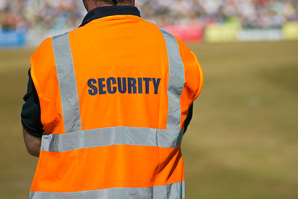 Man in fluorescent orange security vest standing on a field  stock photo