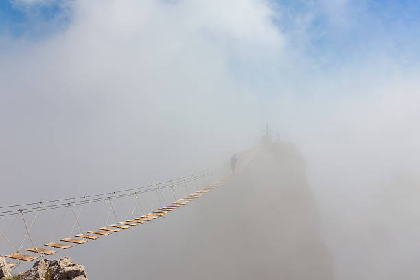Man in fog over chasm Man crossing the chasm on the hanging bridge in fog (focus on the middle of bridge) footbridge stock pictures, royalty-free photos & images