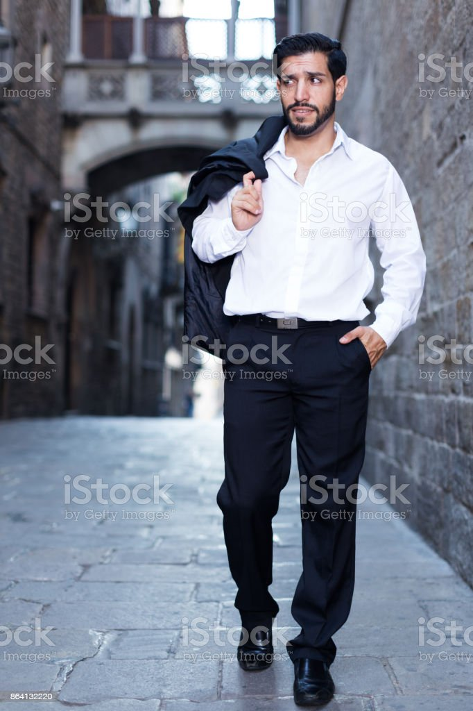 Man in formal clothes strolling past old castle royalty-free stock photo