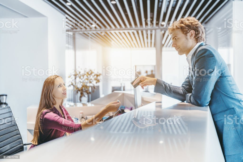 Man in formal suit giving plastic card to female receptionist stock photo