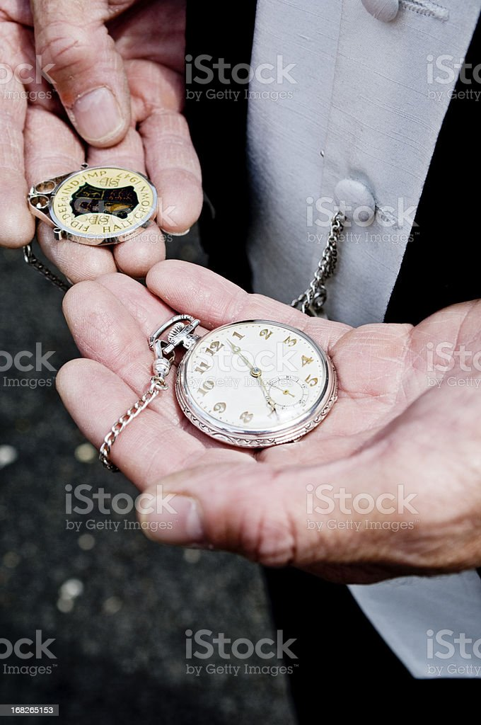 Man in formalwear holding antique pocket watch and fob stock photo