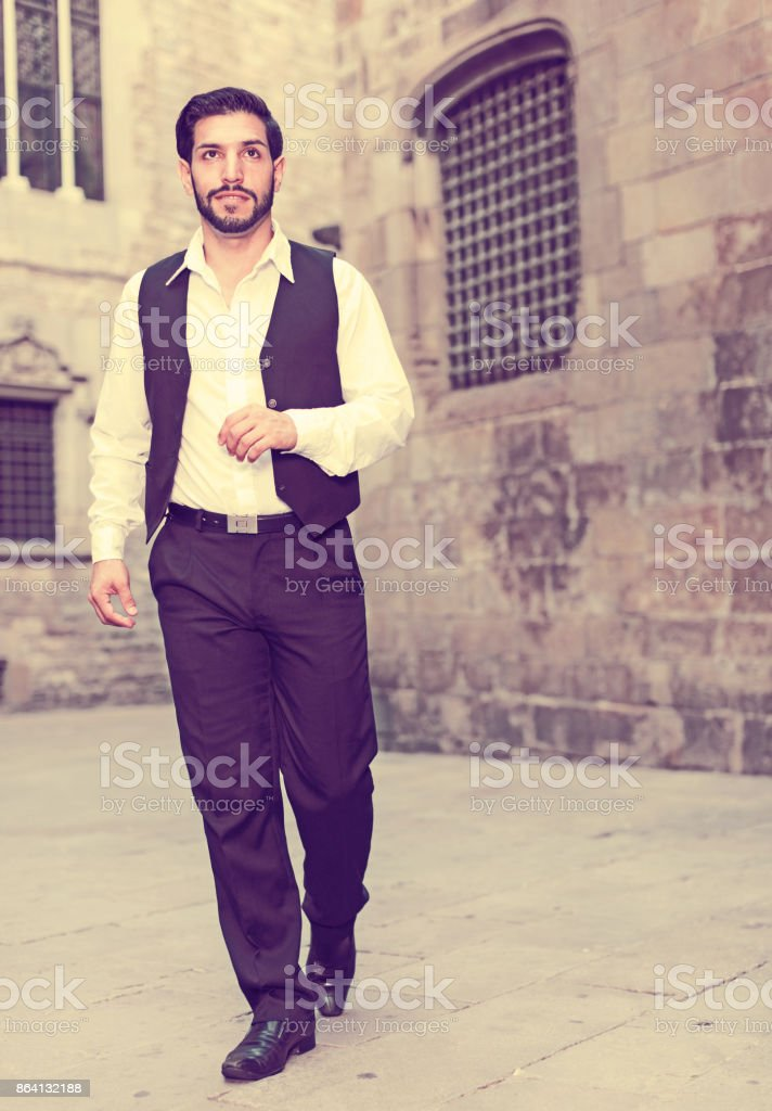 Man in formalwear walking along street royalty-free stock photo