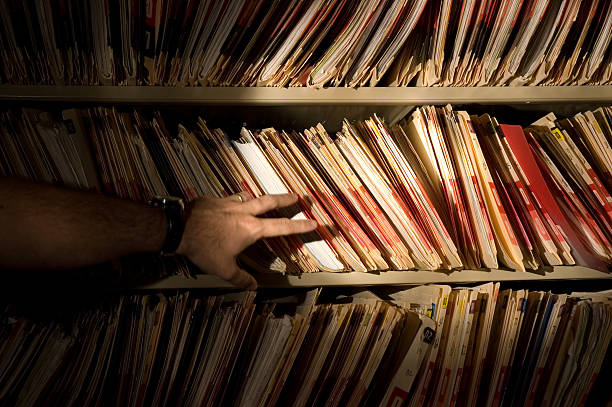 A man in front of a bookshelf of medical records stock photo