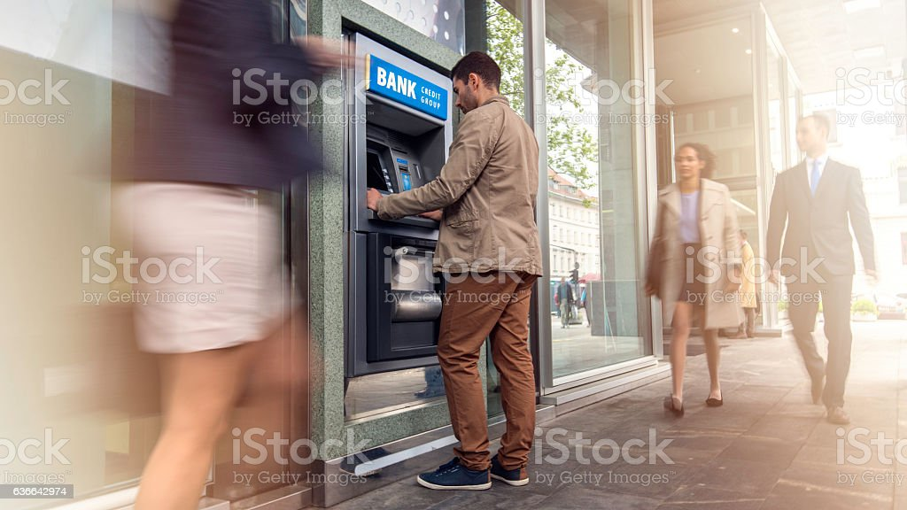 Man in front of an ATM machine ストックフォト