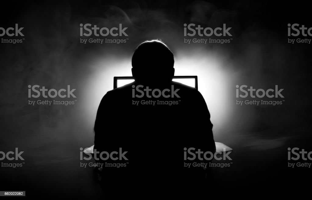 Man in front of computer. Dark night room with smoke stock photo