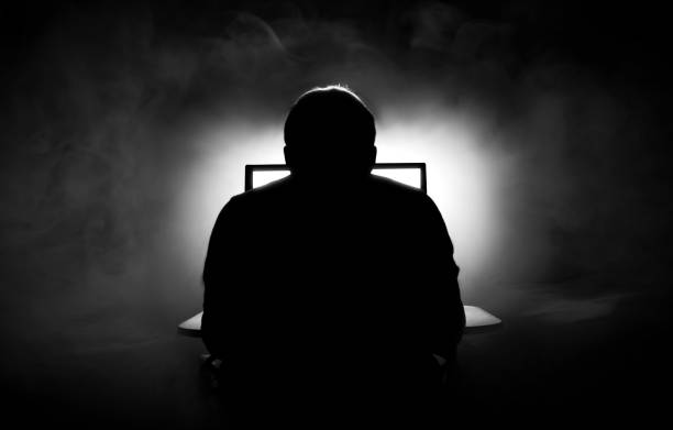 man in front of computer. dark night room with smoke - hacker stock photos and pictures