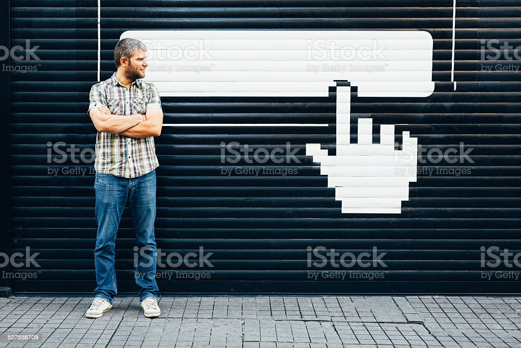 Man in front of empty bilboard and pointer stick stock photo