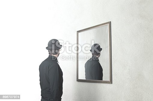 istock man in front of mirror that reflect his back, surreal magritte concept 898707974
