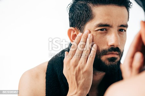 istock Man in front of mirrror looking at his wrinkles 882698982