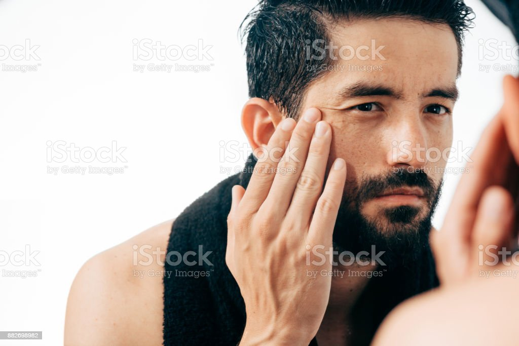 Man in front of mirrror looking at his wrinkles stock photo
