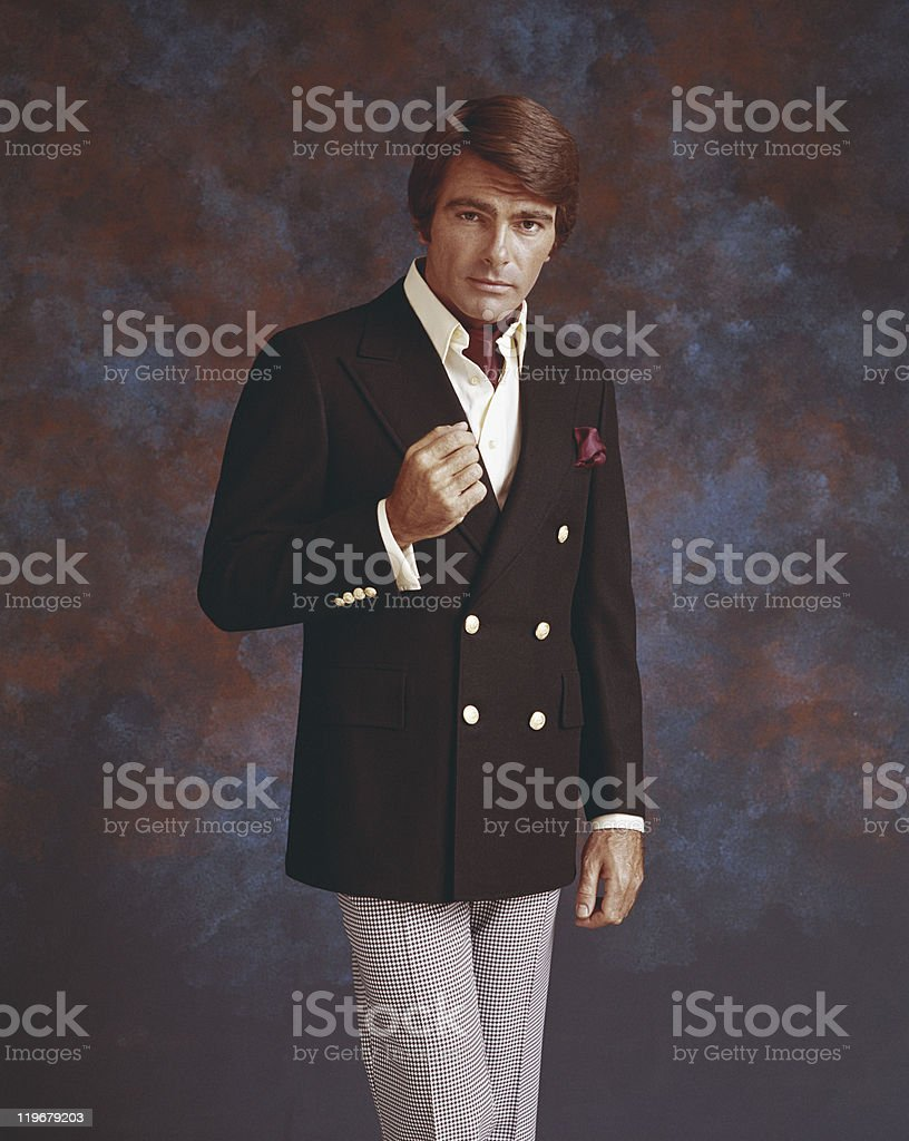 Man in full suit standing against multi coloured background, portrait stock photo