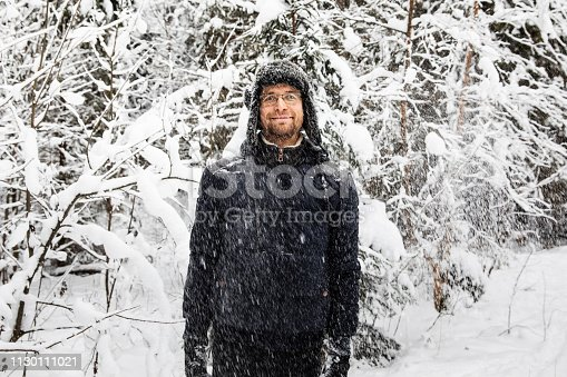 Man in fur winter hat with ear flaps smiling portrait. Extreme in the forest