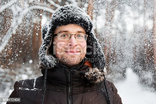 istock Man in fur winter hat with ear flaps smiling portrait 629412404