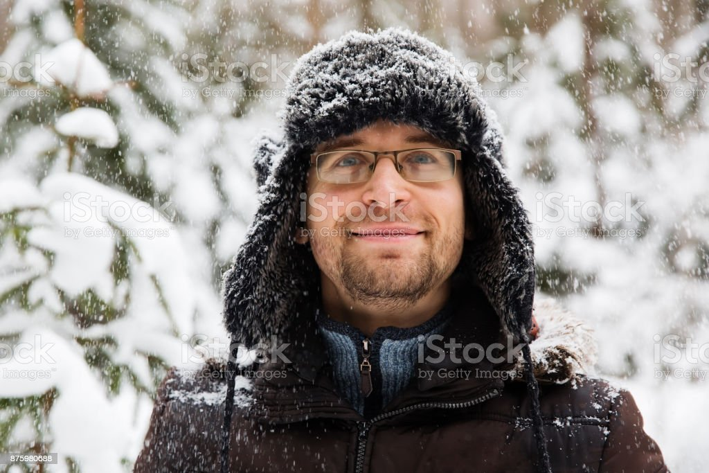 Man in fur winter hat with ear flaps smiling portrait stock photo
