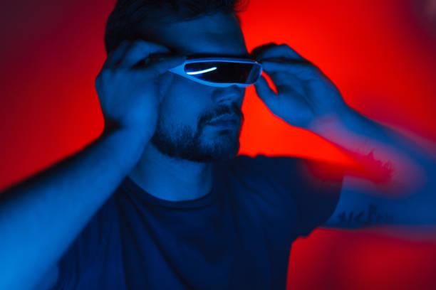man in futuristic vr glasses - vr red background imagens e fotografias de stock