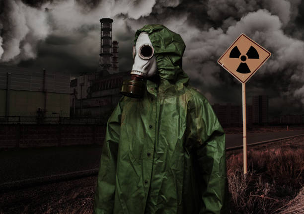 Man in gas mask and cloak of chemical protection on abandoned road. stock photo