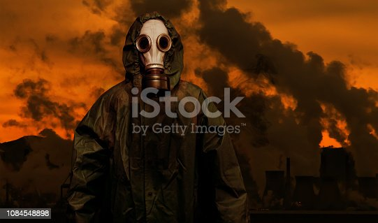 Man in gas mask and cloak of chemical protection with heavy industry plant on background, air pollution concept