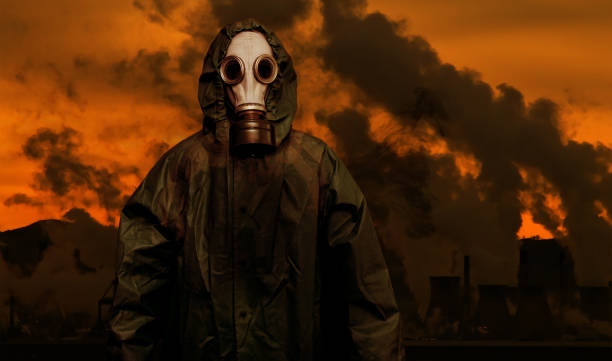 Man in gas mask and cloak of chemical protection with heavy industry plants stock photo