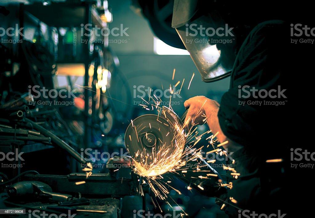 Man in gear grinding metal on steel in spare part workshop stock photo