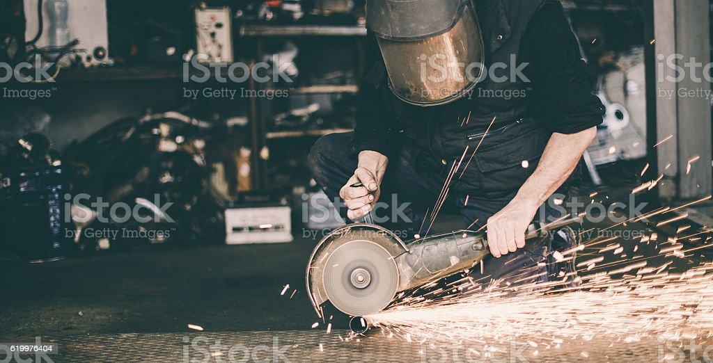 Man in gear grinding metal stock photo